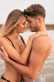 Vista frontal do casal abraçando na praia