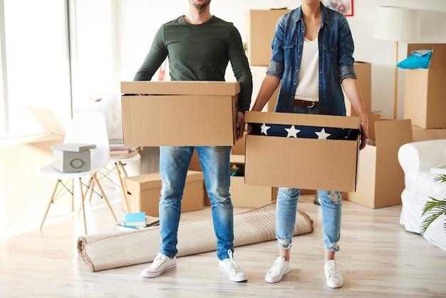 Vista frontal do casal com caixas de papelão