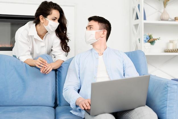 Vista frontal do casal com máscaras em casa