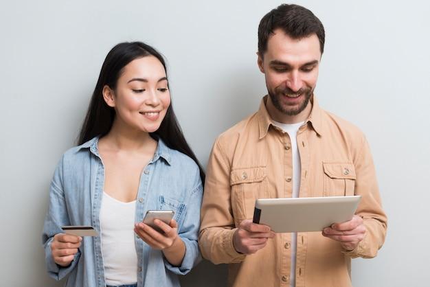 Vista frontal do casal de compras on-line em diferentes dispositivos