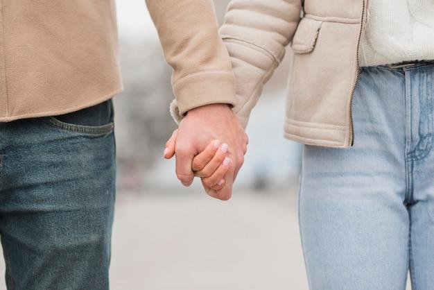 Vista frontal do casal de mãos dadas