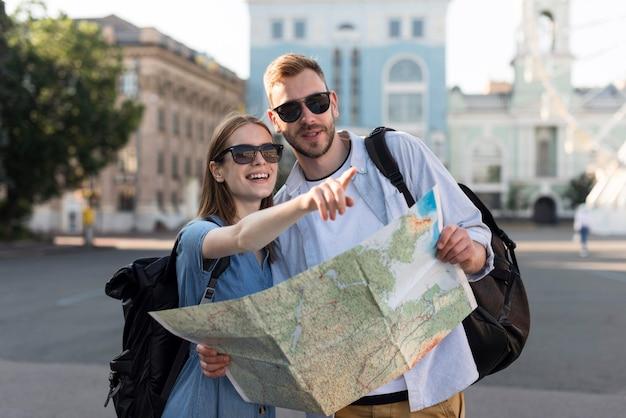 Vista frontal do casal de turistas apontando algo enquanto segura o mapa