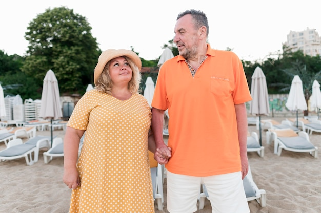 Vista frontal do casal de turistas mais velhos na praia de mãos dadas