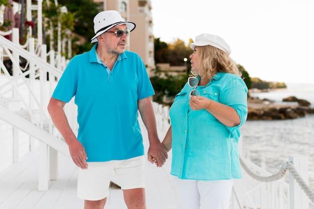 Vista frontal do casal de turistas mais velhos na praia