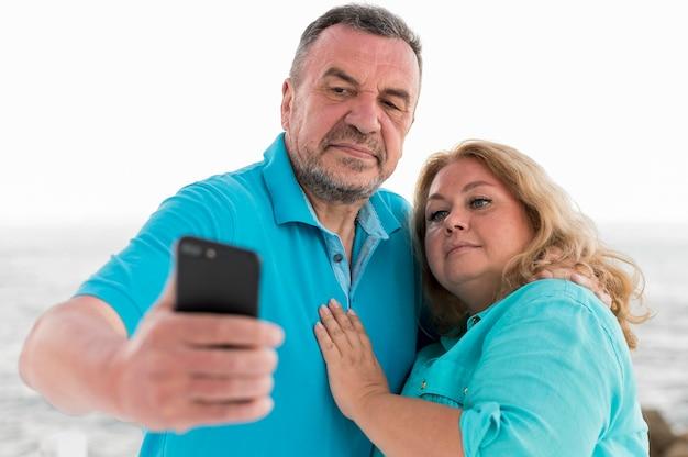Vista frontal do casal de turistas mais velhos tomando uma selfie
