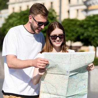 Vista frontal do casal de turistas olhando para o mapa
