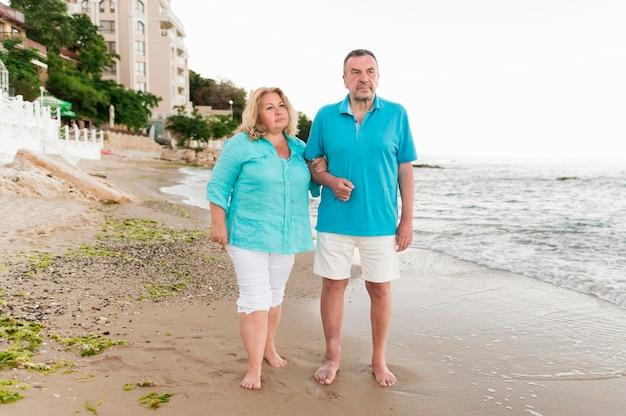 Vista frontal do casal de turistas sênior na praia