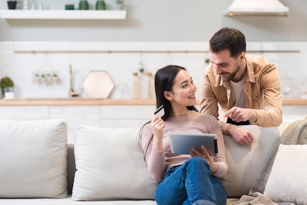 Vista frontal do casal do sofá decidir o que comprar on-line