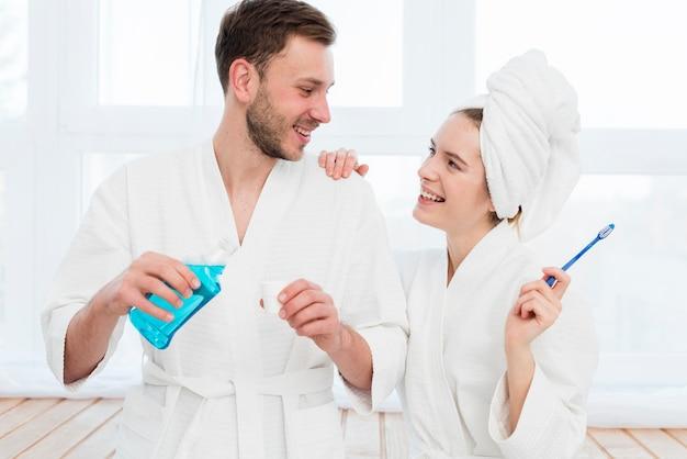 Vista frontal do casal em roupões de banho com enxaguatório bucal e escova de dentes