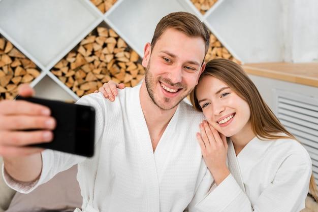 Vista frontal do casal em roupões de banho tomando uma selfie