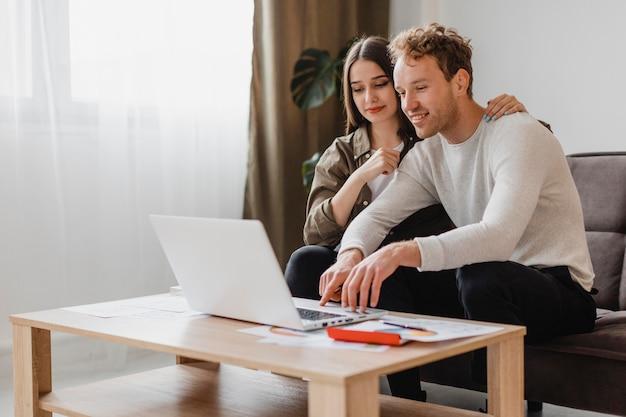Vista frontal do casal fazendo planos para reformar a casa juntos