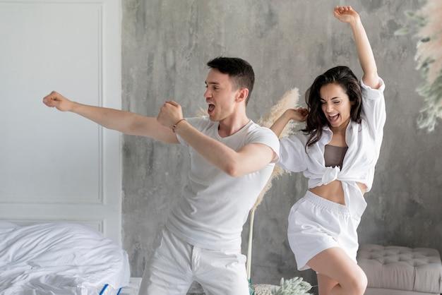 Vista frontal do casal feliz dançando em casa