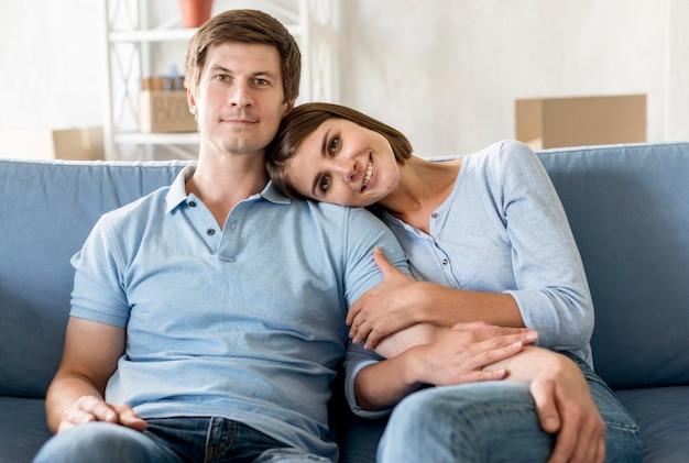 Vista frontal do casal feliz no sofá enquanto faz as malas para se mover