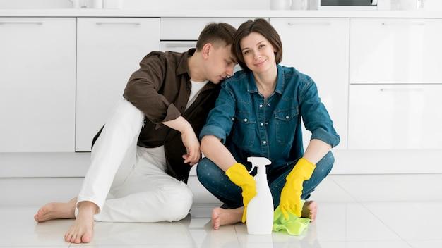 Vista frontal do casal limpando a casa