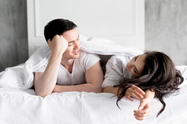 Vista frontal do casal na cama em casa