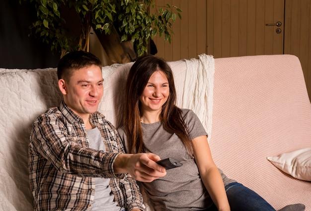 Vista frontal do casal no sofá, segurando o controle remoto