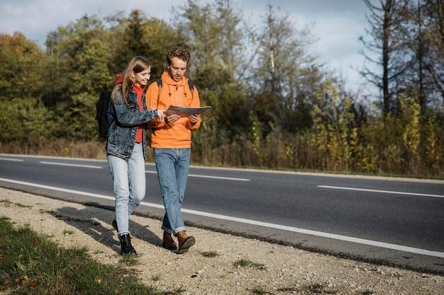 Vista frontal do casal segurando o mapa e caminhando pela estrada