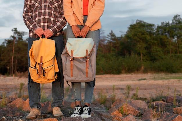Vista frontal do casal segurando suas mochilas com espaço de cópia