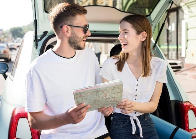 Vista frontal do casal sorridente com mapa