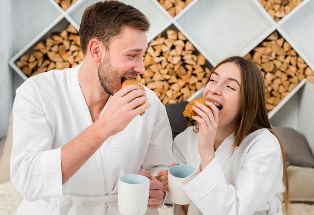 Vista frontal do casal sorridente comendo croissant