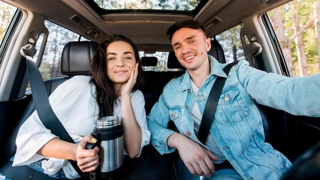 Vista frontal do casal tirando uma selfie no carro