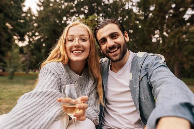 Vista frontal do casal tirando uma selfie