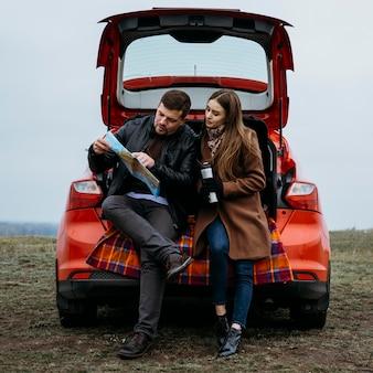 Vista frontal do casal verificando um mapa no porta-malas do carro