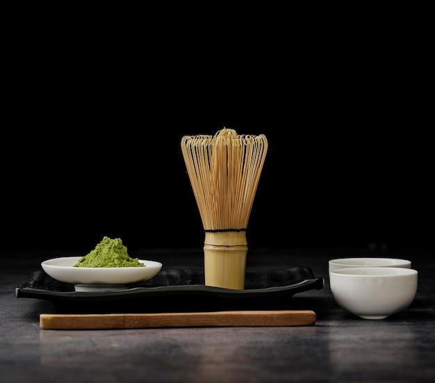 Vista frontal do chá matcha com batedor de bambu