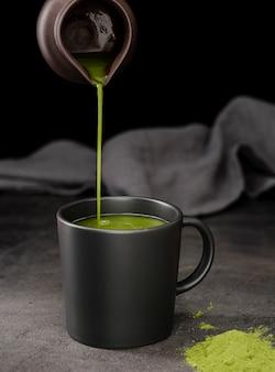 Vista frontal do chá matcha derramado em copo