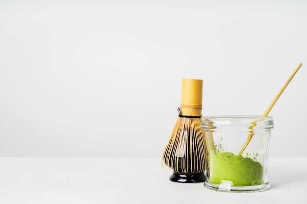 Vista frontal do chá verde japonês orgânico e ferramentas chasen bambu whis