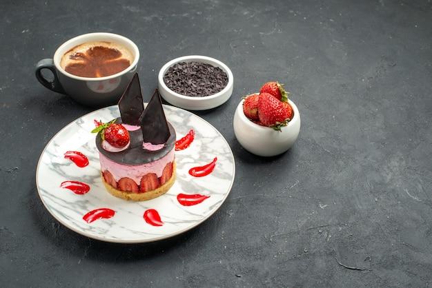 Vista frontal do cheesecake de morango em tigelas de prato branco com morangos e chocolate uma xícara de café no espaço livre de fundo escuro