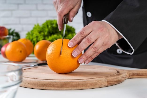 Vista frontal do chef cortando uma laranja