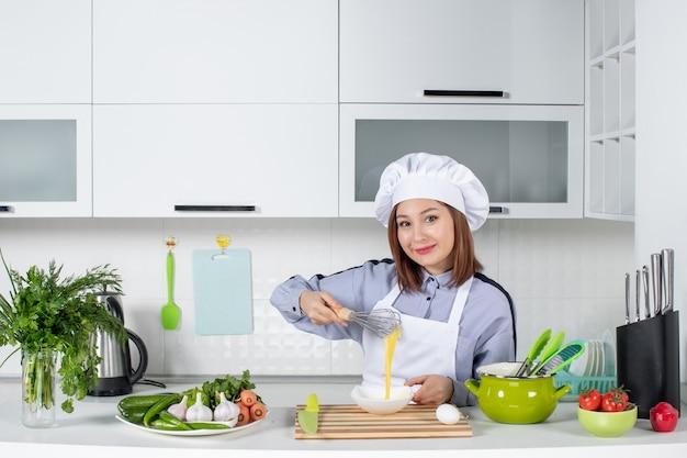 Vista frontal do chef feliz e vegetais frescos com equipamento de cozinha e mistura do ovo em uma tigela branca na cozinha branca