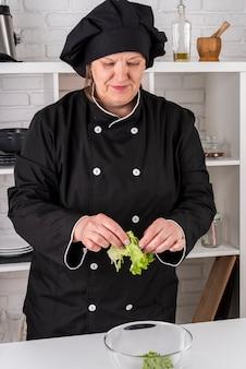 Vista frontal do chef feminino rasgando salada na tigela