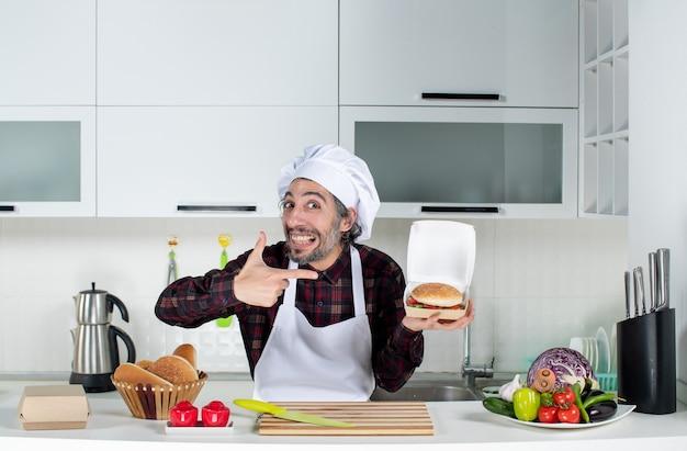 Vista frontal do chef masculino apontando para um hambúrguer na mão na cozinha