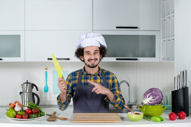 Vista frontal do chef masculino com legumes frescos e cozinhando com utensílios de cozinha e apontando para cima segurando uma faca na cozinha branca