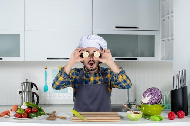 Vista frontal do chef masculino com legumes frescos e cozinhando com utensílios de cozinha e segurando a comida na frente do olho na cozinha branca