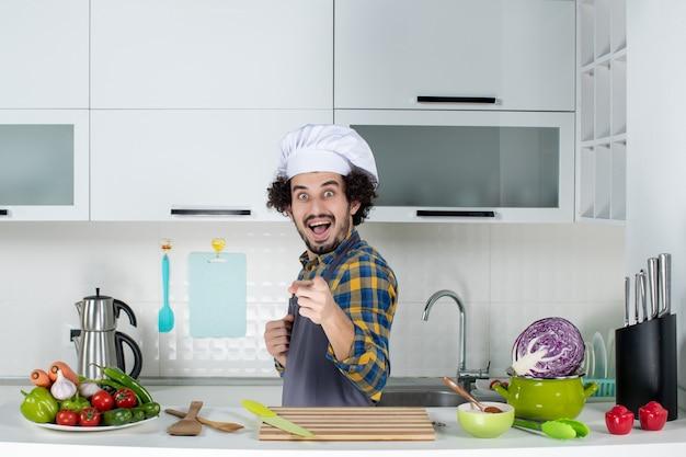 Vista frontal do chef masculino feliz e positivo com legumes frescos e cozinhando com utensílios de cozinha e na cozinha branca