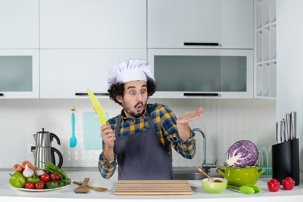 Vista frontal do chef masculino perguntando-se com legumes frescos, cozinhando com utensílios de cozinha e segurando uma faca na cozinha branca