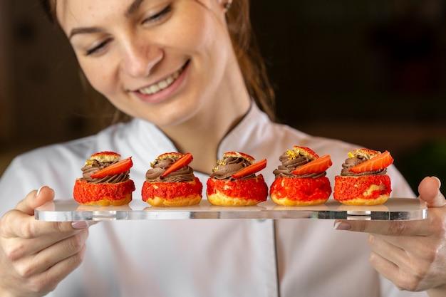 Vista frontal do chef olhando um prato com comida