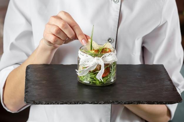 Vista frontal do chef segurando comida deliciosa