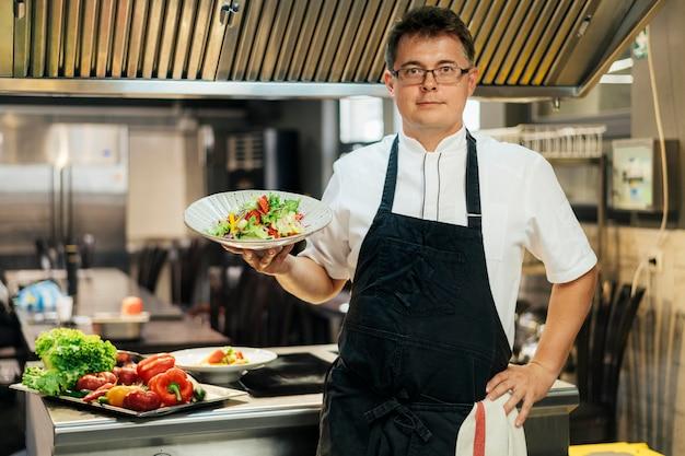 Vista frontal do chef segurando o prato