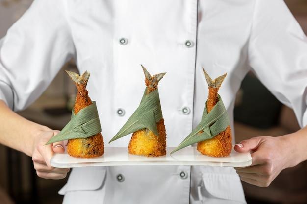 Vista frontal do chef segurando um prato com peixe