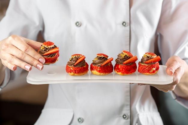 Vista frontal do chef segurando um prato de comida delciious