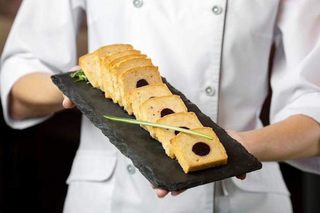 Vista frontal do chef segurando um prato de comida delcious