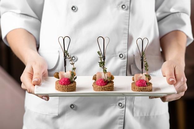 Vista frontal do chef segurando um prato de comida