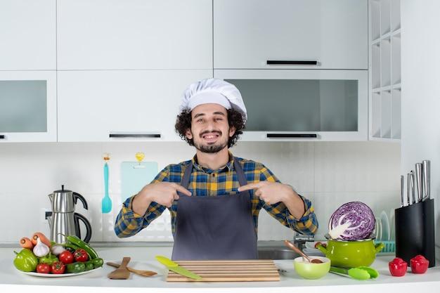 Vista frontal do chef sorridente com legumes frescos, cozinhando com utensílios de cozinha e apontando a si mesmo na cozinha branca