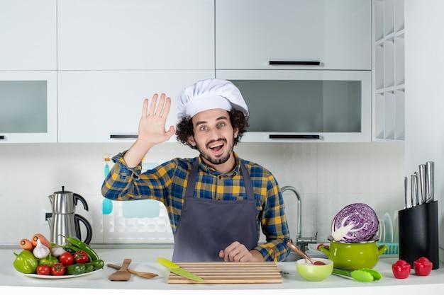 Vista frontal do chef sorridente com legumes frescos, cozinhando com utensílios de cozinha e dizendo olá na cozinha branca