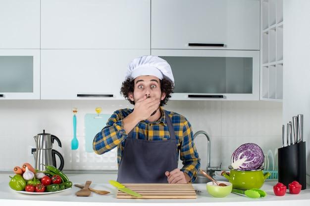 Vista frontal do chef surpreso com legumes frescos e cozinhando com utensílios de cozinha e apontando para frente e fechando a boca na cozinha branca