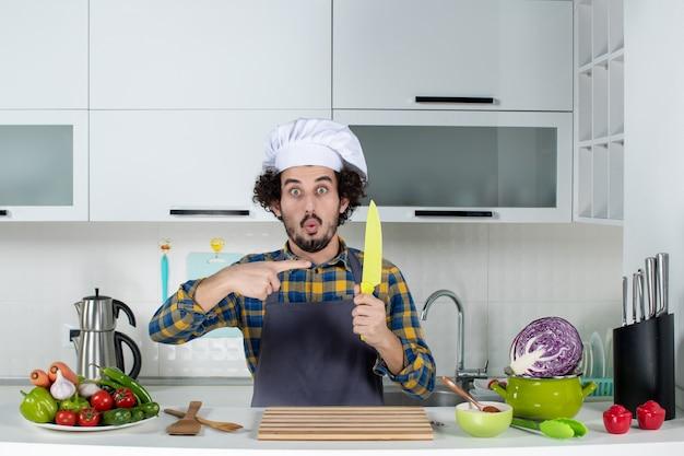 Vista frontal do chef surpreso com legumes frescos e cozinhando com utensílios de cozinha e faca apontando na cozinha branca